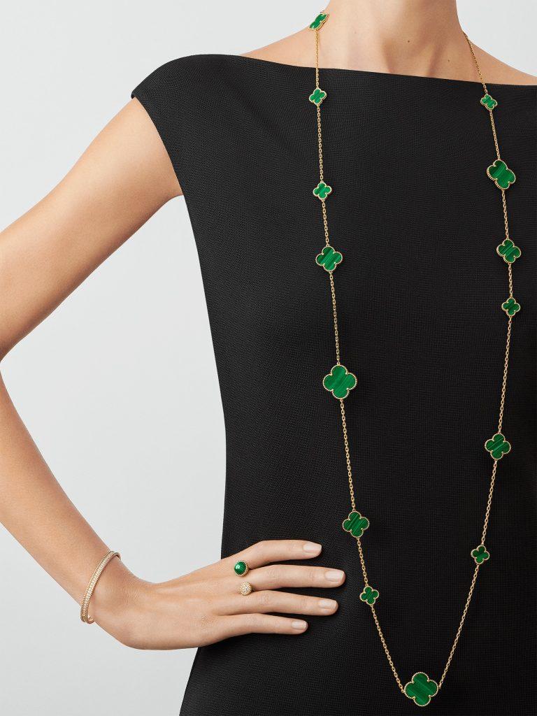 Femme portant un long sautoir Alhambra de la marque de bijoux de luxe Van Cleefs and Arpels. En or doré et trèfles en malachite.