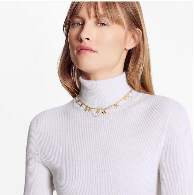 Mannequin portant un collier ras de cou à breloques dorées de la marque Louis Vuitton.