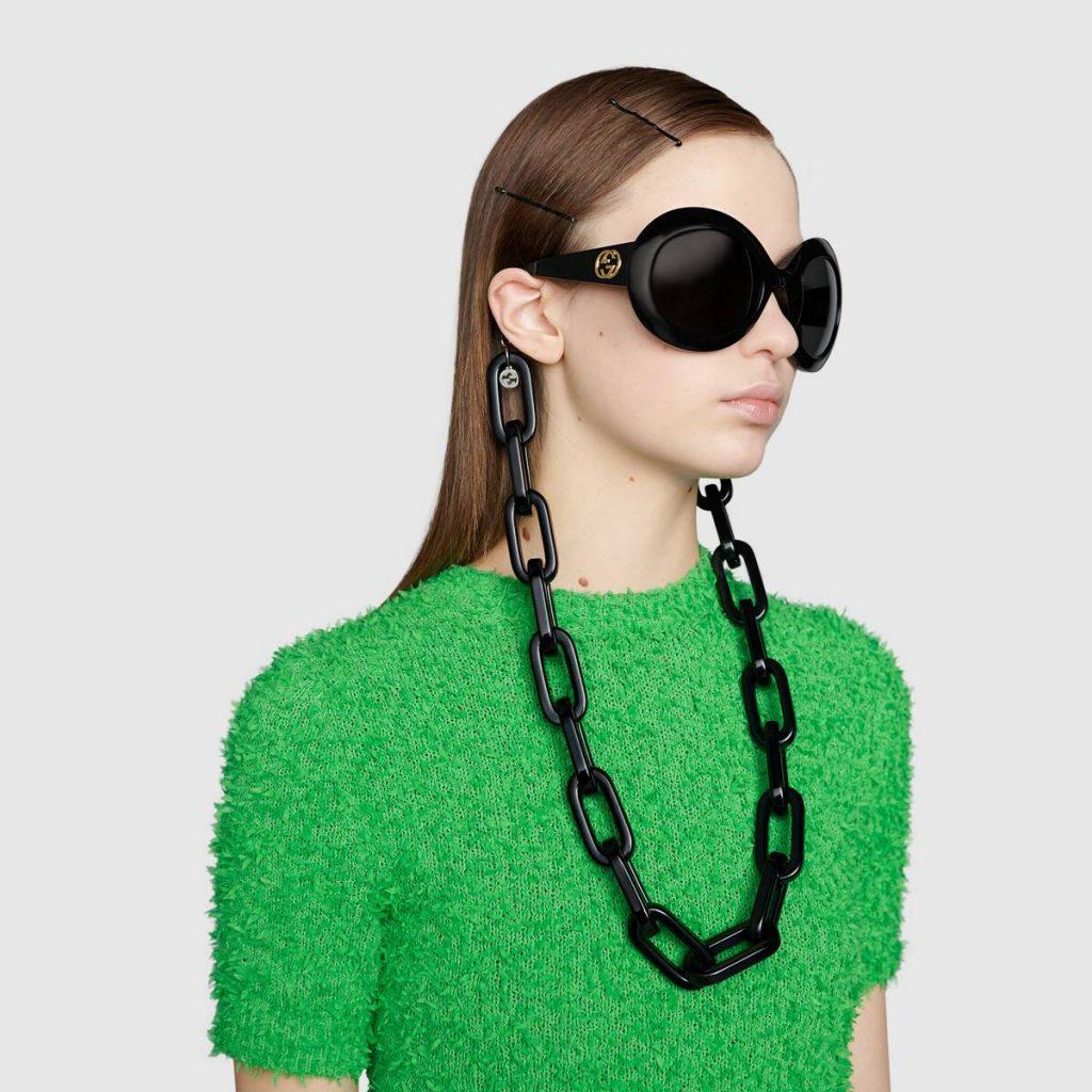 Mannequin femme portant des lunettes de soleil et une maxi chaîne à lunettes en résine - GUCCI