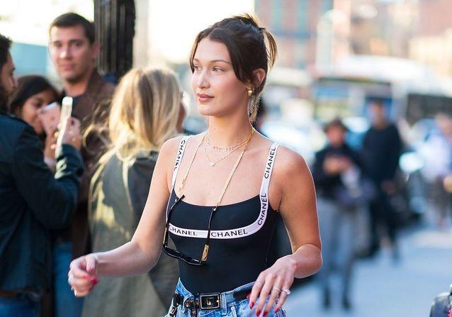 La mannequin Gigi Hadid, dans les rues de New York, portant des chaînes de lunettes pour un style casual chic. Parissima, votre grossiste de mode, suit les tendances au plus près.